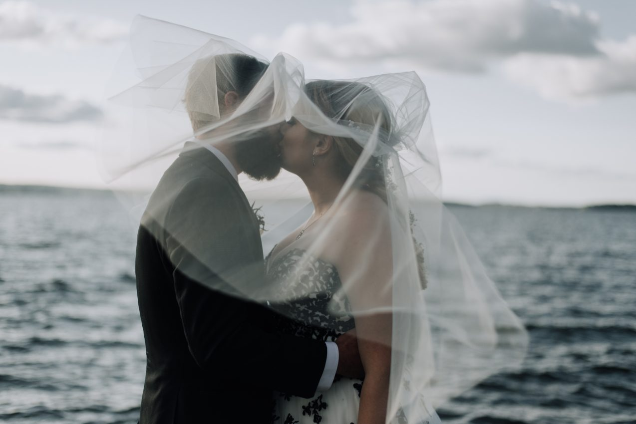 Bride and Groom kissing under veil in the wind