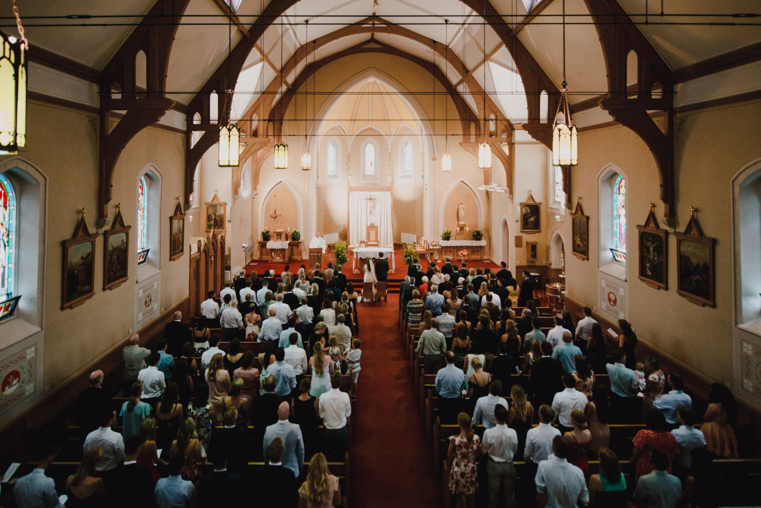 The guests and bride and groom all stand in the church during the ceremony
