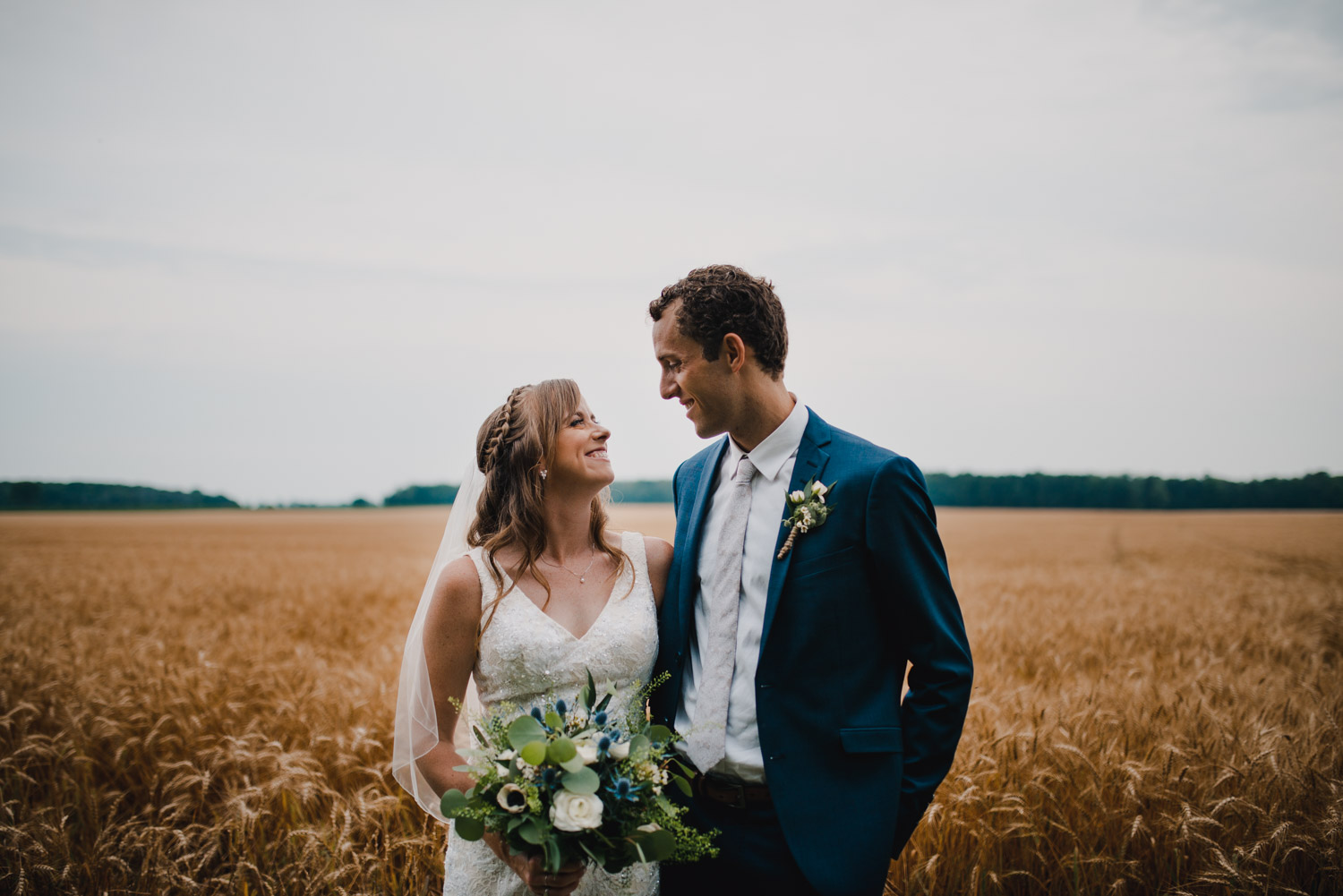 The bride and groom looking at eachother lovingly while standing in front of a wheat field