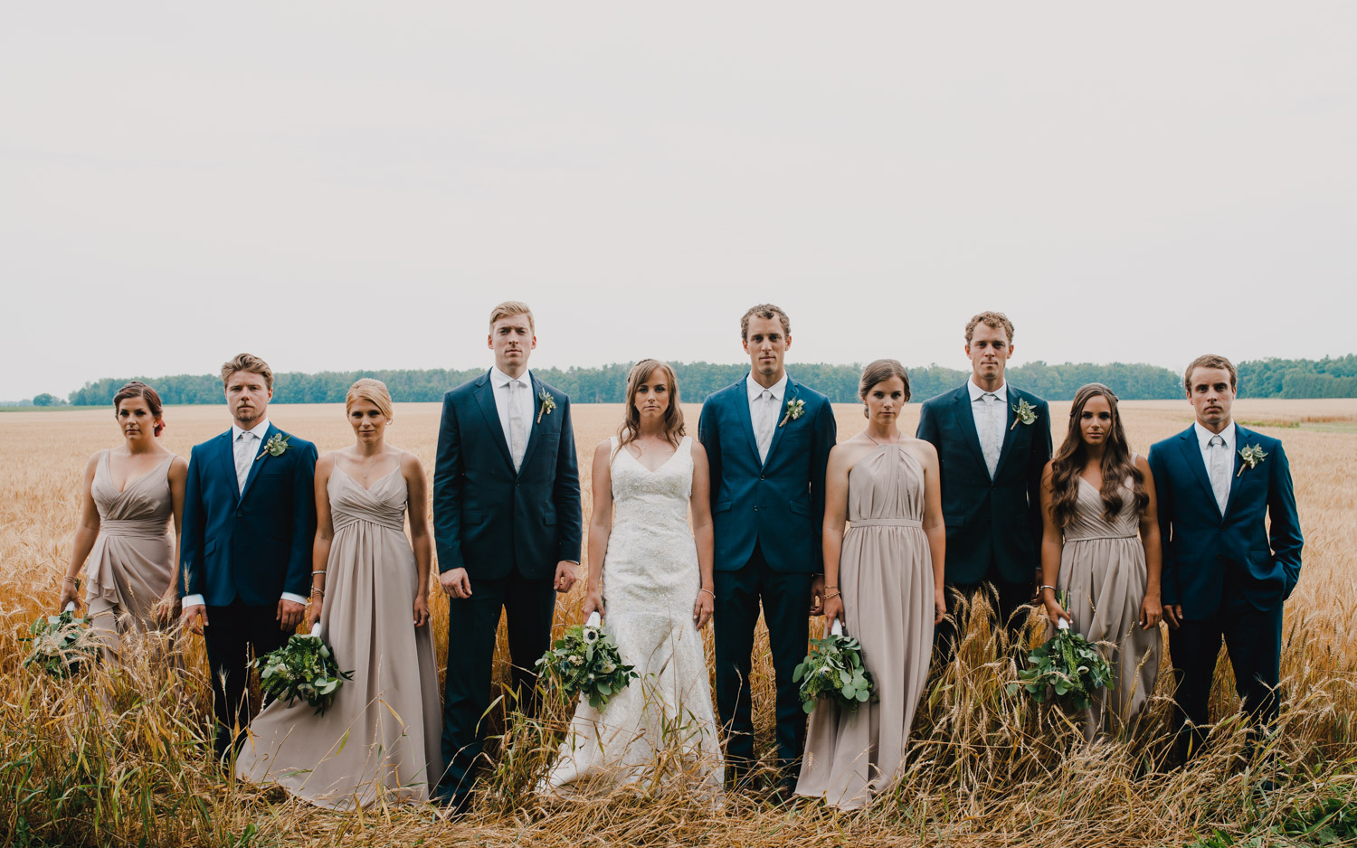 "The wedding party stand together in an ""American Gothic"" style pose"