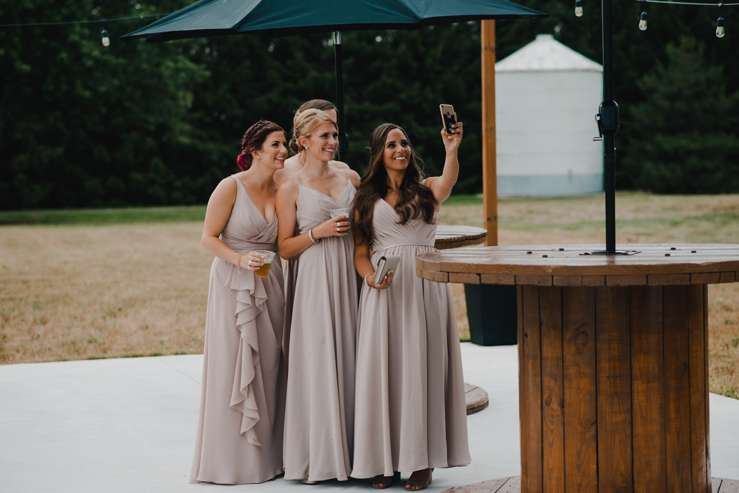 The bridesmaids all crowd together to pose for a selfie