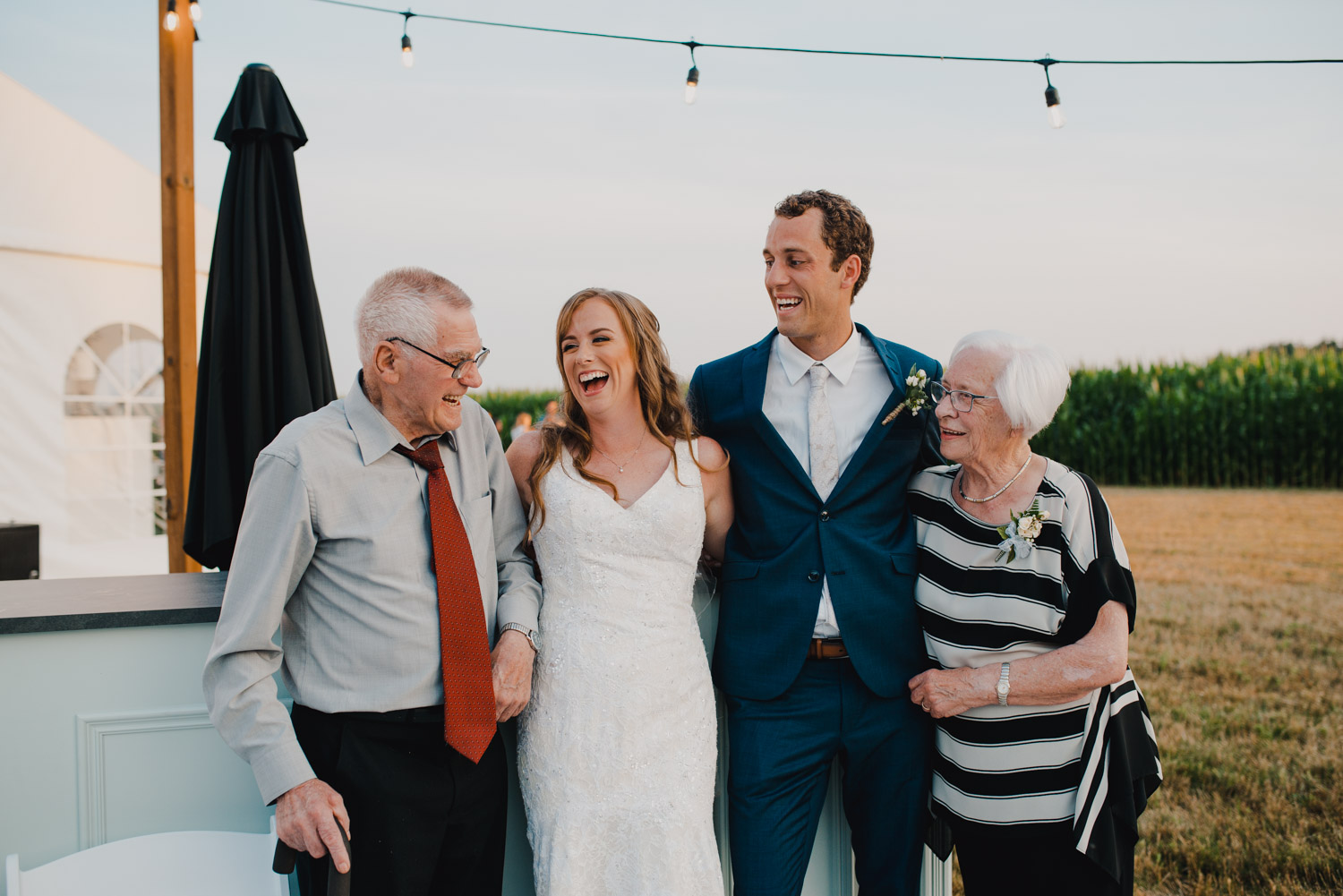 The bride and groom and their grandparents laughing together