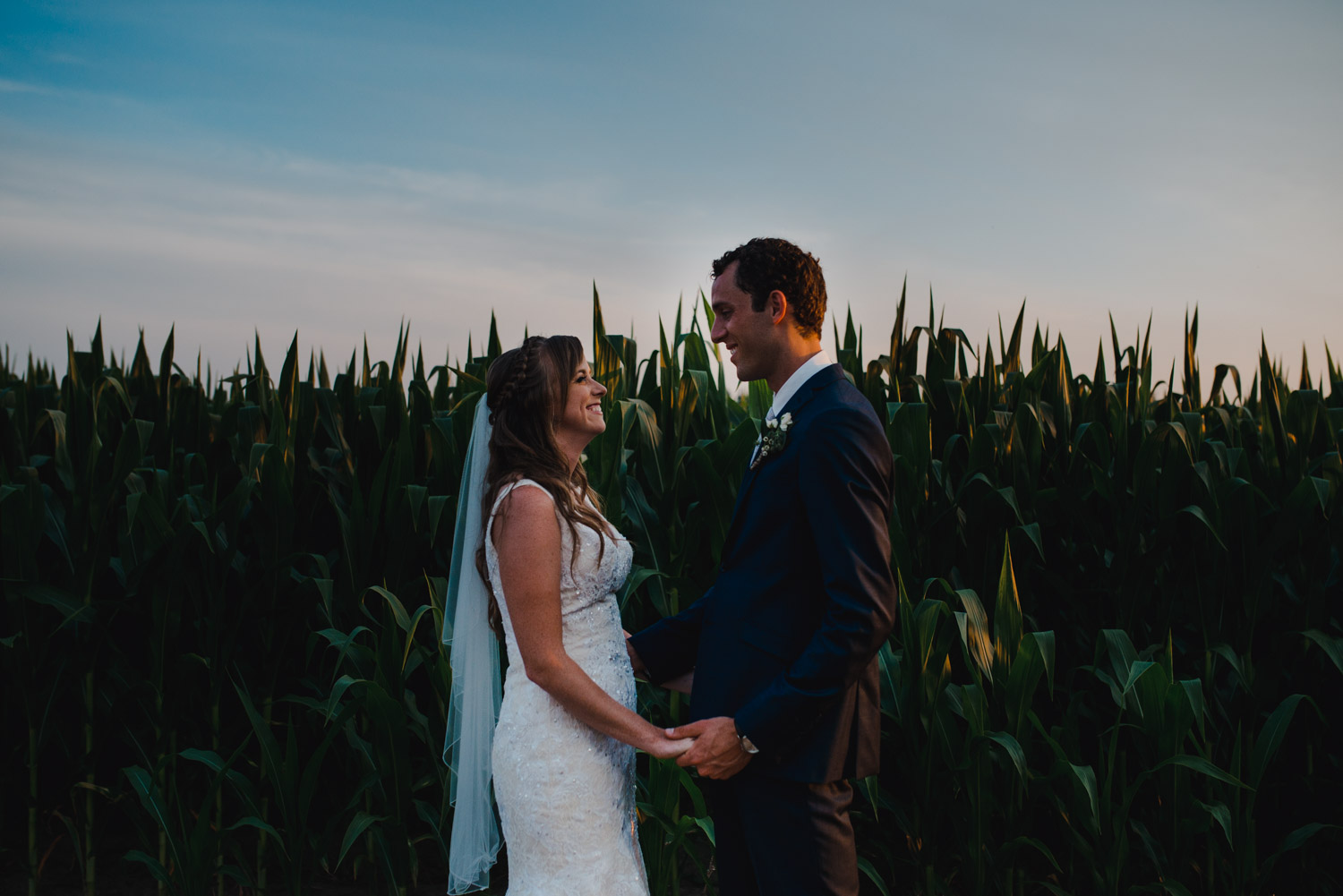 The bride and groom looking at each other and laughing in front of a cornfield at sunset