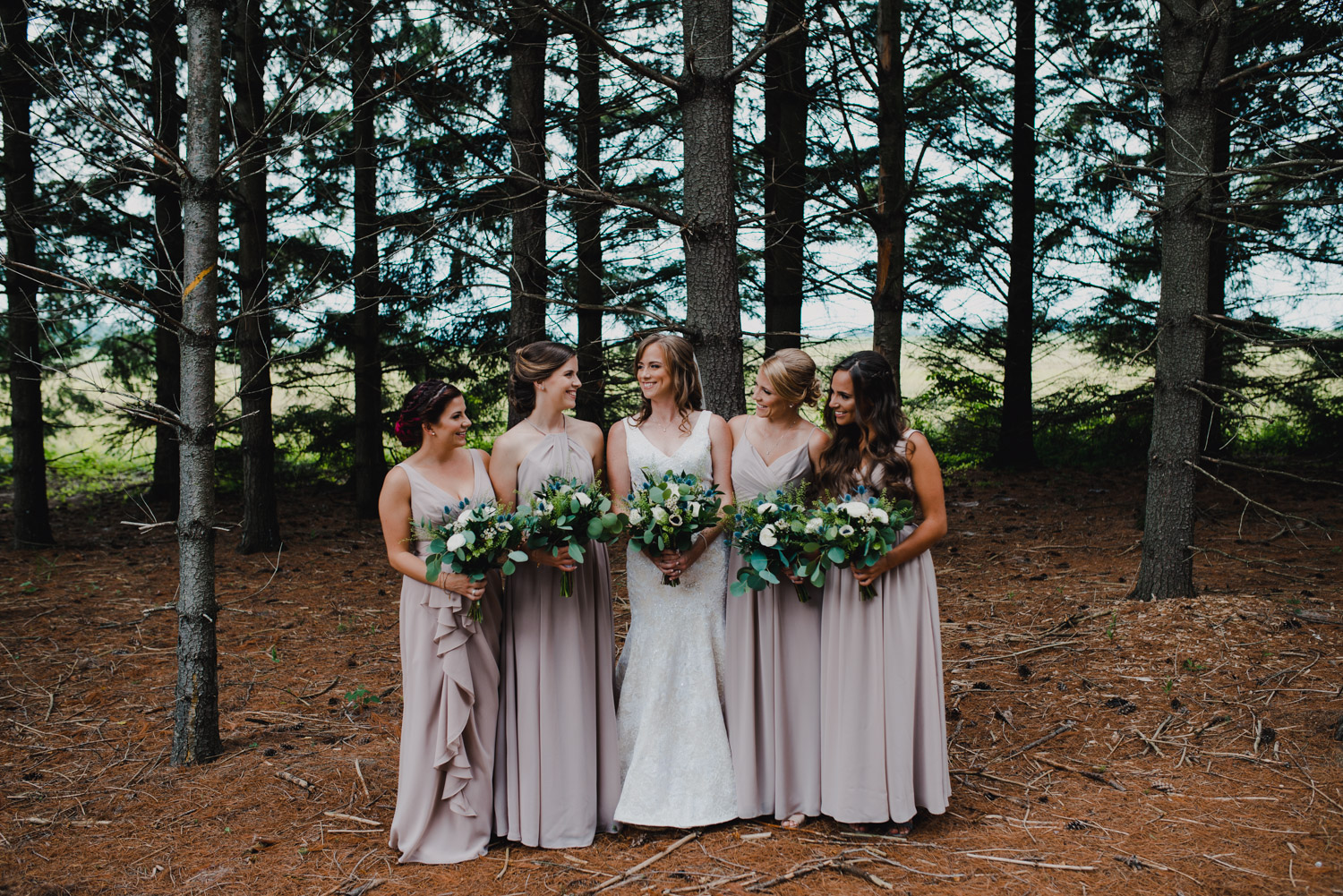 Bridesmaids laughing together and standing with their flowers