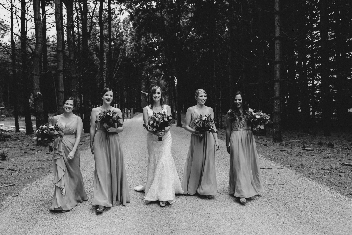 The bridesmaids laughing and walking with their flowers